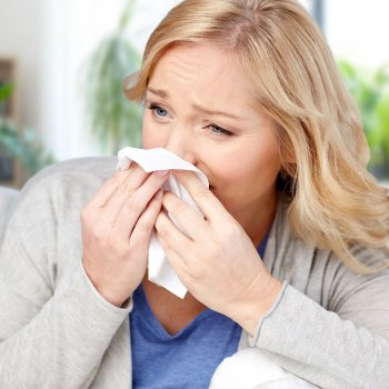 woman at home with hay fever symptoms sneezing